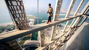 Venäläinen Oleg kävelee palkin päällä Cayan Tower -rakennuksen huipulla Dubaissa.