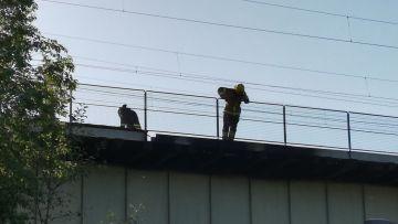 Brandmän granskar järnvägsbro i Tammerfors efter att plankorna på bron fattade eld.
