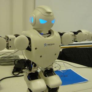En robot står på ett bord med händerna utsträckta.