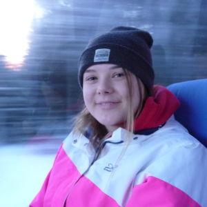 En ung kvinna med mössa på huvudet sitter i en buss.