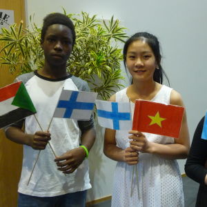 Tre barn står med flaggor i hand. En sudansk pojke viftar med Sudans och Finlands flaggor, en vietnamesisk flicka med Vietnams och Finlands flaggor och en bosnisk flicka med Bosniens och Tysklands flaggor.
