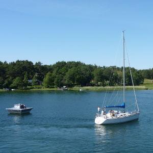 En tömningsstation för septiktankar flyter på vattnet. Bredvid syns en segelbåt.