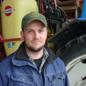 Jonas Lillgäls står vid en traktor.