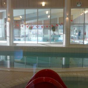 I förgrunden en liten simbassäng. Bakom en rad med fönster en större simbassäng.