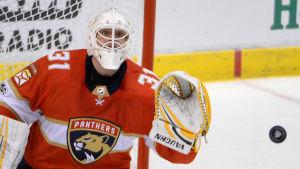 Rödklädde ishockeymålvakten Antti Niemi på knä för att rädda puck.