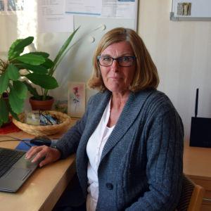 Marianne Löfström-Lahti i Pixneklinikens personalrum. Hon sitter framför en dator vid fönstret.