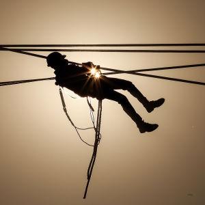 Indisk arbetare drar kraftledningar i Mumbai, Indien