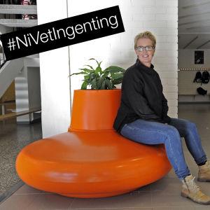 Linda Fagerudd, skolkurator i Pedersöre, sitter  på plastsoffa med #NiVetIngenting i bildens hägra hörn