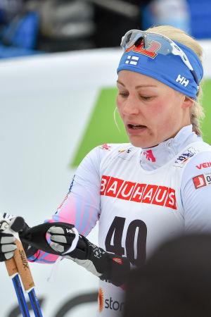 Besviken Anne Kyllönen tar av sig skidstavarna efter målgång.