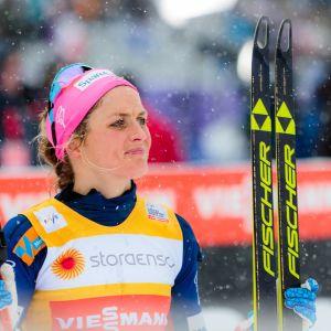 Therese Johaug med skidor i vänster hand och stavar i höger hand.