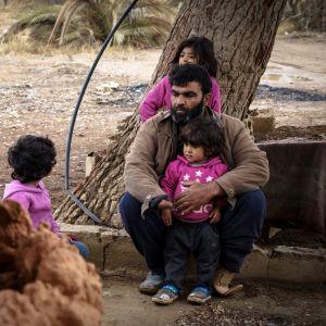 Raqqalainen Muhammed ja hänen kolme lastaan istuvat puun juurella