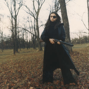 Frigga (Christina Lindberg) står svartklädd med ett vapen i hand i en höstlig skog.