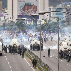 Polisen avfyrar tårgas mot tusentals demonstranter som blockerade en motorväg i Caracas.