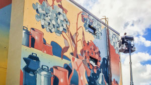 Mies maalaa suurikokoista seinämaalausta telalla nosturista käsin.