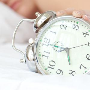Person i sängen, väckarklocka i förgrunden