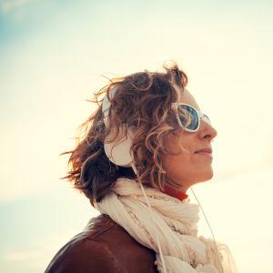 Kvinna i solglasögon har hörlurar på sig och lyssnar på musik.