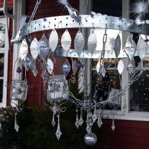 En hemgjord kristallkrona med stomme av spikband och kättingar, dekorerad med lila glaspärlor, klara kristaller och bladformade aluminiumbitar. Kristallkronan har ljushållare av återanvända glasburkar.