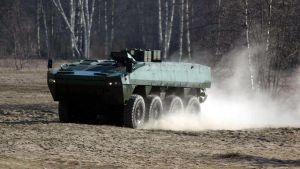 Ett Patria-militärfordon kör på en grusplan.