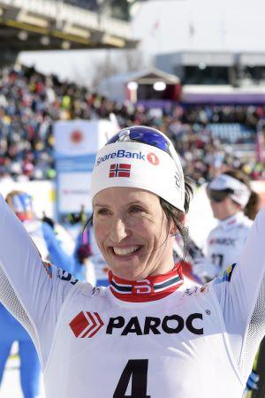 Marit Bjørgen håller händerna i luften