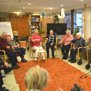 Många äldre personer sitter inomhus på stolar i en ring. De ser glada ut och har händerna i luften.