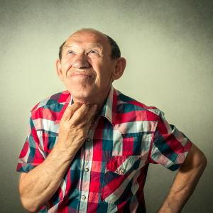 Äldre man i rutig skjorta ser fundersam ut