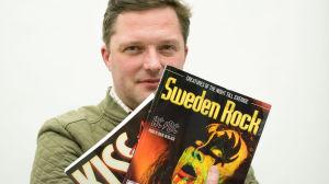 Henric Creutz poserar med tidningar med Kiss på omslaget