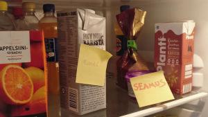 """Kylskåp med gula post it lappar med namnen """"Muriel"""" och """"Seamus"""" på havermjölktölk och grynostsburk."""