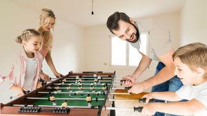 Drömlik bild med familj som spelar foosball i lägenhet utan andra möbler