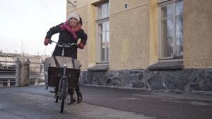 Linda Sundberg med cykel och halsduk framför gult stenhus.