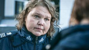 Näyttelijä Kaarina Hazard poliisin univormussa katsoen toista ihmistä silmiin.