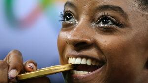 Simone Biles biter på sin OS-guldmedalj.