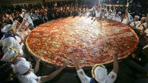 Napolilaiset pizzakokit tuulettavat jättimäisen pizzan ympärillä.