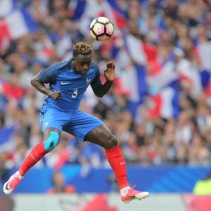 Blåklädde fotbollsspelaren Benjamin Mendy hoppar och nickar bollen.
