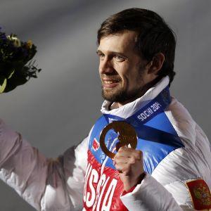 Aleksander Tretjakov håller upp sin medalj.