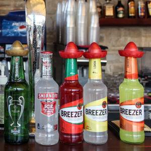 Åtta flaskor med olika alkoholdrycker står uppradade på en bardisk.