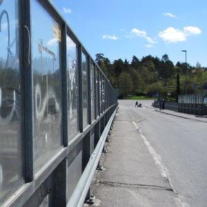 En bro med körfil och trottoar samt skyddsräcken av genomskinlig plast som är klottrat. Sommartid, solen skiner. På bron syns några fotgängare på avstånd.  Under bron skymtar järnvägsspår och ett tåg samt parkerade bilar.