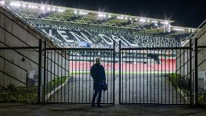 Helena står utanför grindarna vid en upplyst men tom fotbollsarena.