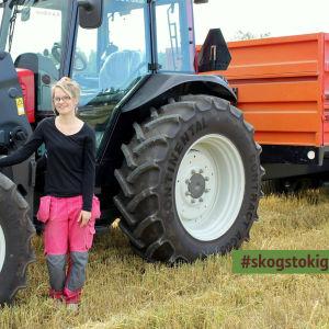 Unga Anna Öman står på en tröskad åkar och lutar sig mot en traktor med vagn. Längst ner i högra hörnet är dekalen #skogstokig inklippt i bilden.