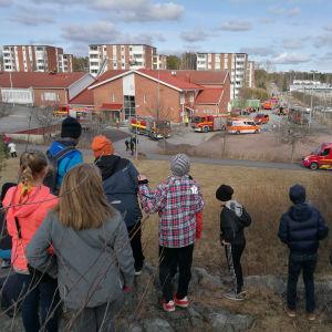 barn följer med räddningsverkets arbete efter brandunge i Karvetin koulu i Nådendal.