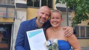 Bild av leende Matias Jungar och Malin Valtonen med diplom och blombukett i handen.