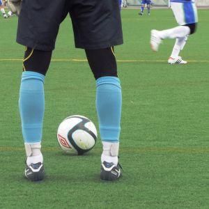 Fotbollsspelare och en fotboll på en gräsplan.