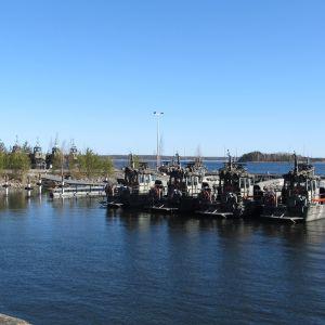 Militärbåtar förtöjda vid en brygga. Sommar, solsken.