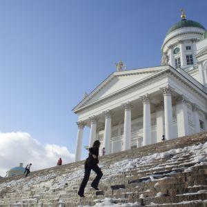 Kvinna springer upp för trappan till Helsingfors domkyrka