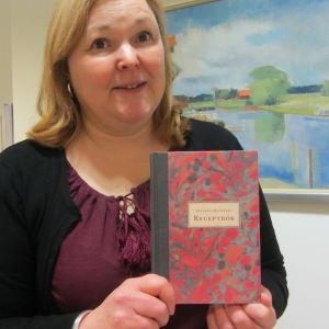 Susanna Widjeskog, amanuens vid Borgå museum med Fredrika Runebergs receptsamling