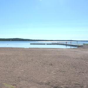 På bilden en nästan tom sandstrand och blå himmel