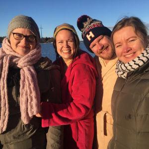 fyra programvärdar på rad på solig brygga i november