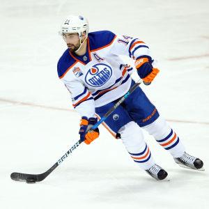Vitklädde hockeyspelaren Jordan Eberle med puck.
