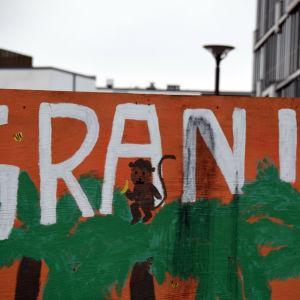 Väggmålning föreställande apa i en palm med texten GRANI ovanför.