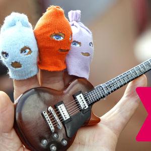 Hand med små ansiktsmasker på tre av fingrarna samt en liten leksakselgitarr i handflatan.