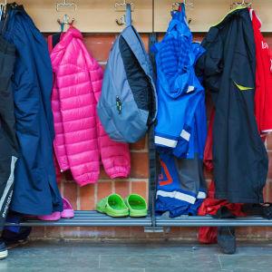 Barnkläder hänger i skolkorridor